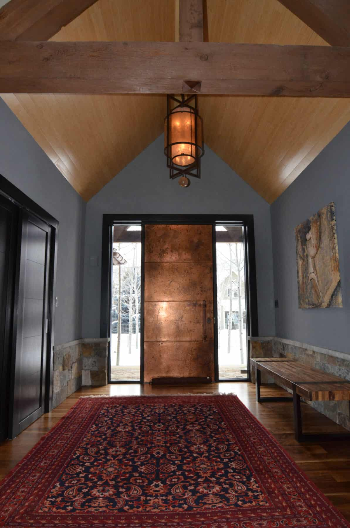 Hand made Copper Entry Door with Matching Amber Shade Chandelier in Aspen, Colorado Custom Home. Luxury Home Building Interiors