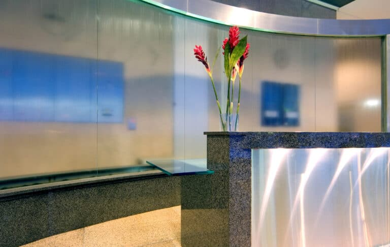 Custom Curved Glass Water Fountain Feature Behind Stone and Metal Reception Desk by Commercial Builder & General Contractor Structural Enterprises