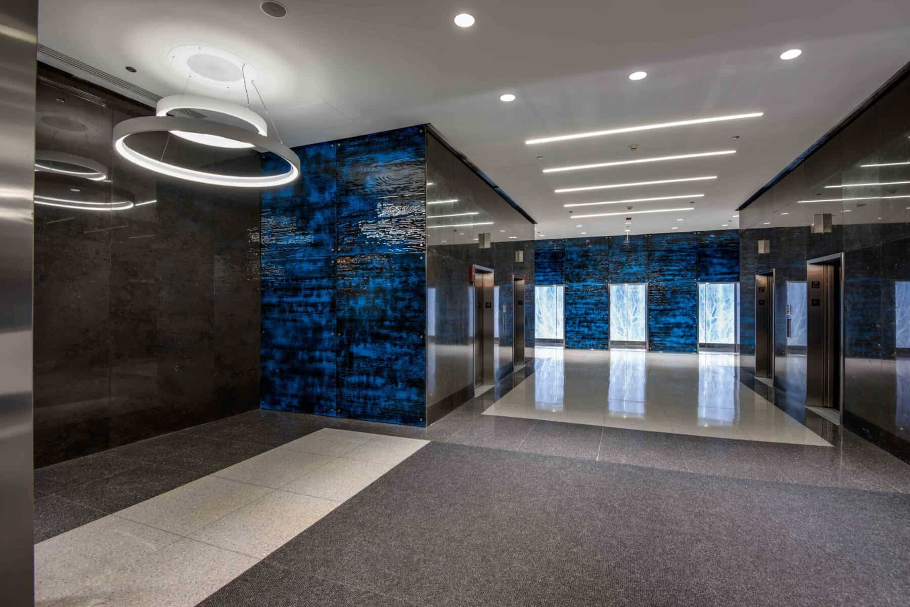 Modern Lobby Remodel with Blue Glass Wall Panels and Suspended LED Lights by Commercial Builder & General Contractor Structural Enterprises
