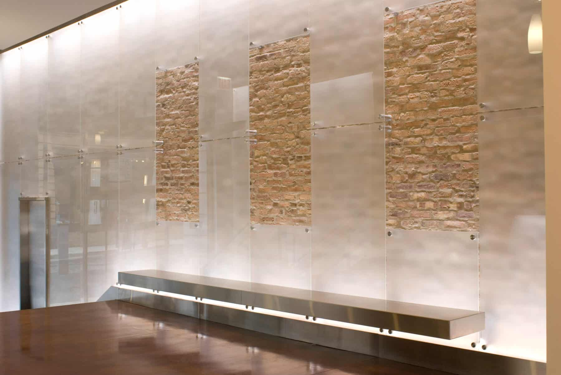 Custom Etched Glass Wall Panels with Metal Floating Bench on Brick Wall for West Jackson Lobby Remodel by Commercial Builder & General Contractor Structural Enterprises